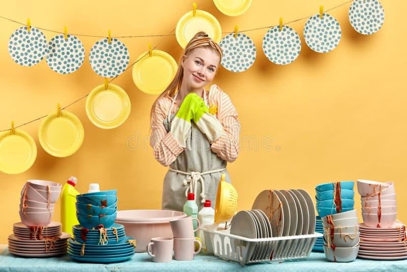 Uśmiechnięta kobieta w rękawiczkach i fartuch pozycja za stołem z brudnymi naczyniami obrazy royalty free
