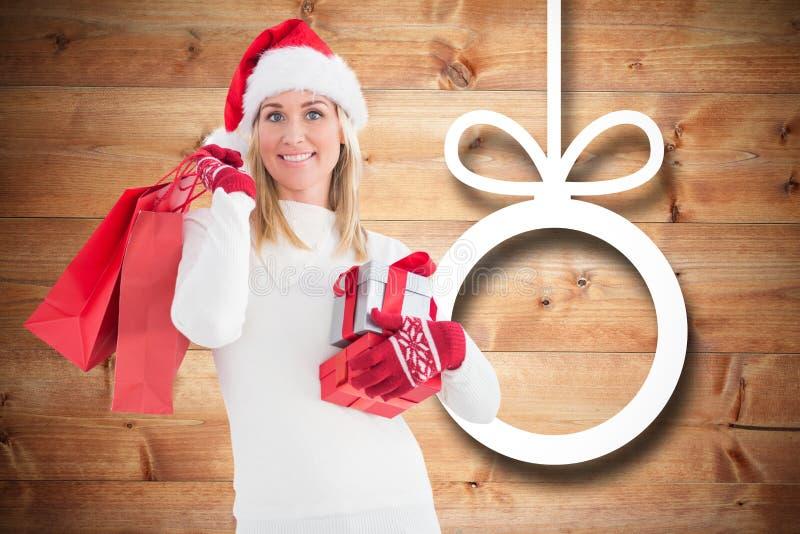 Uśmiechnięta kobieta w Santa mienia bożych narodzeń kapeluszowych prezentach i torba na zakupy zdjęcie royalty free