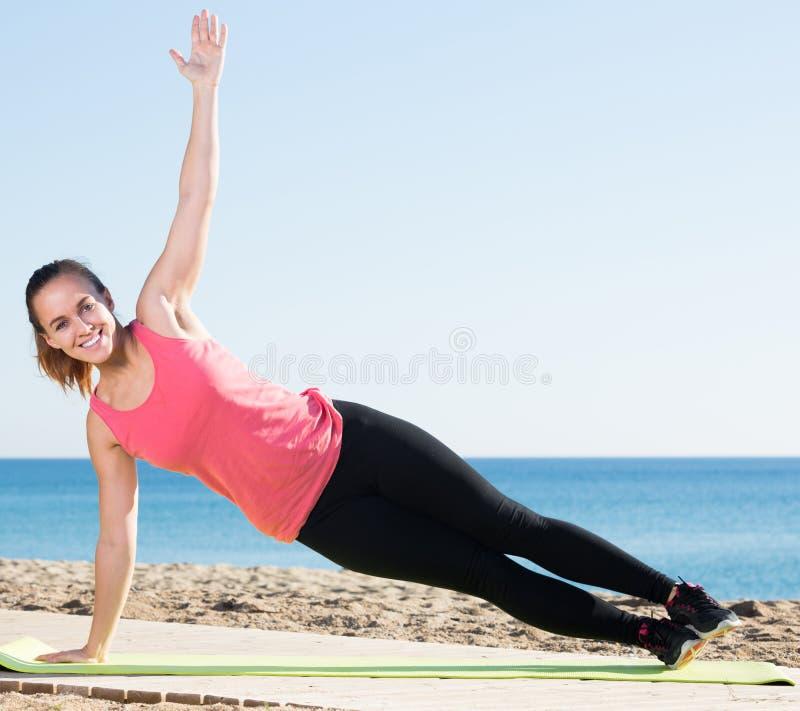 Uśmiechnięta kobieta w sportswear szkoleniu przy morze plażą obrazy stock