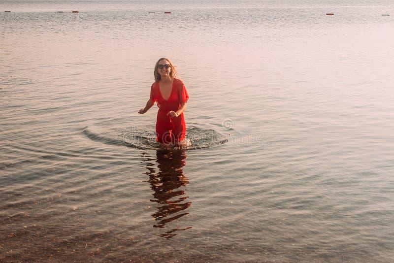 Uśmiechnięta kobieta w tunika bieg przez morze zdjęcia stock