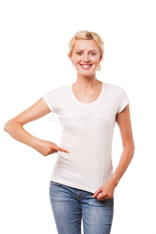 Uśmiechnięta kobieta wskazuje przy pustą białą koszulką zdjęcia stock