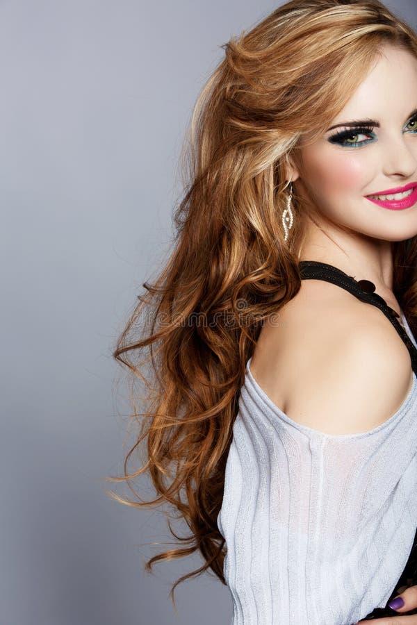 Uśmiechnięta kobieta z długą kędzierzawego włosy i menchii pomadką zdjęcia royalty free