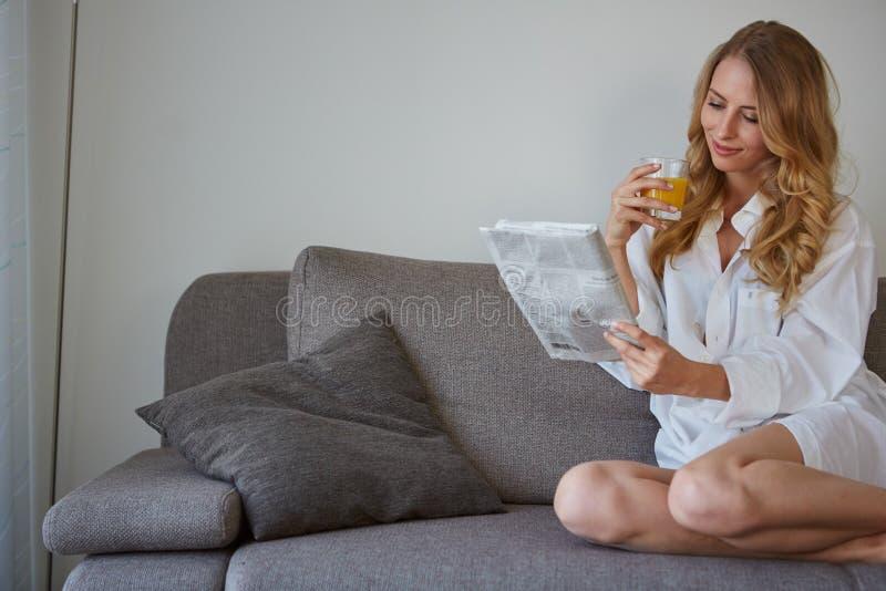 Uśmiechnięta kobieta z filiżanka kawy czytelniczym magazynem zdjęcie stock