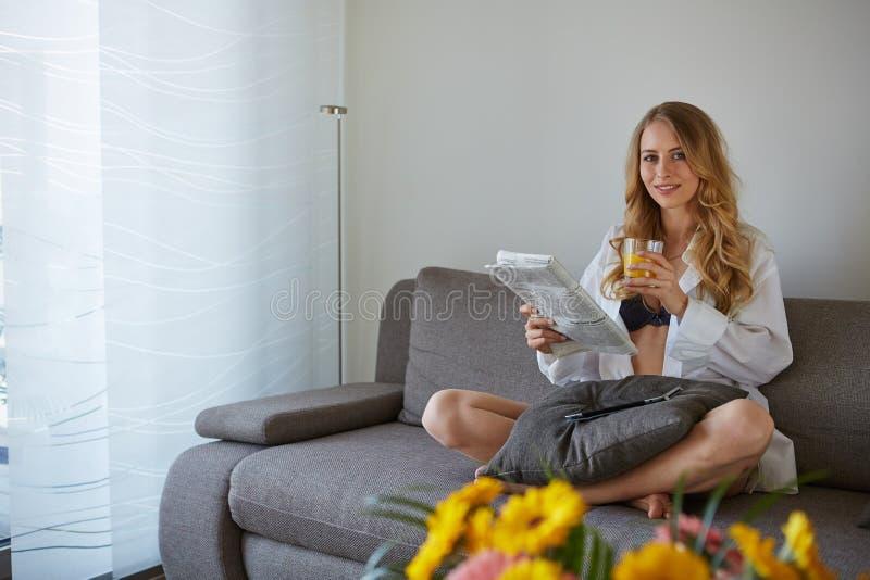 Uśmiechnięta kobieta z filiżanka kawy czytelniczym magazynem fotografia stock