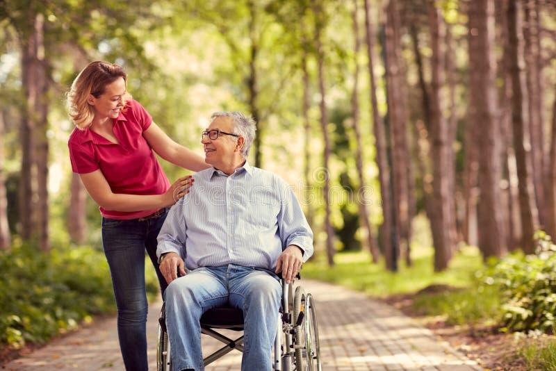 Uśmiechnięta kobieta z jej niepełnosprawnym ojcem w wózku inwalidzkim zdjęcia royalty free