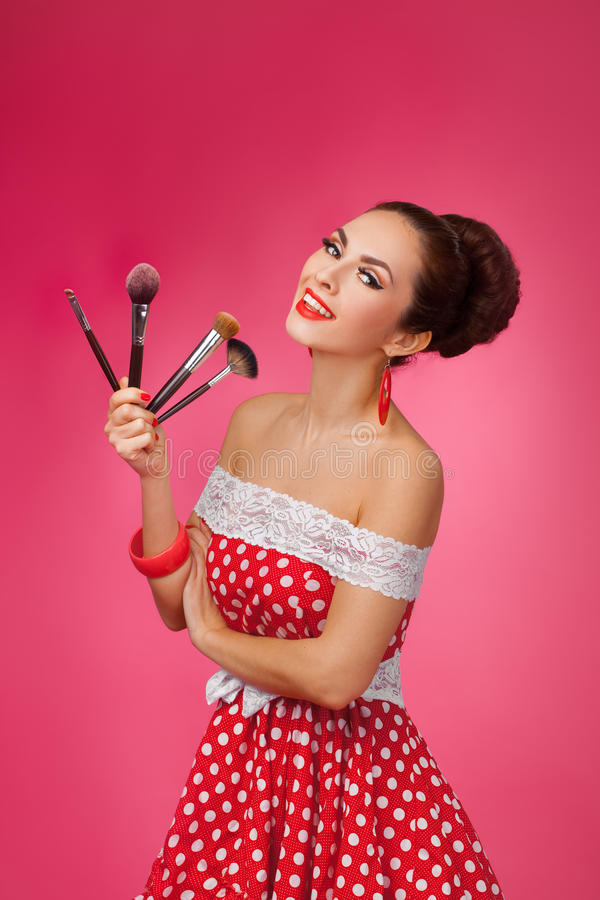 Uśmiechnięta kobieta z makeup muśnięciami Stoi fotografia stock