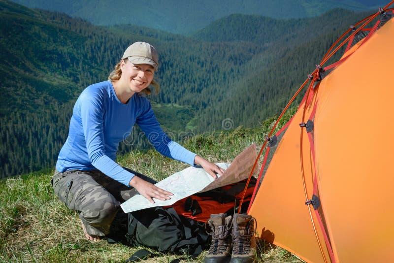 Uśmiechnięta kobieta z mapą w górach fotografia royalty free