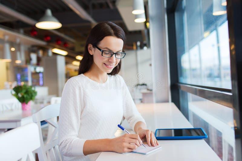 Uśmiechnięta kobieta z pastylka komputerem osobistym przy kawiarnią obraz stock