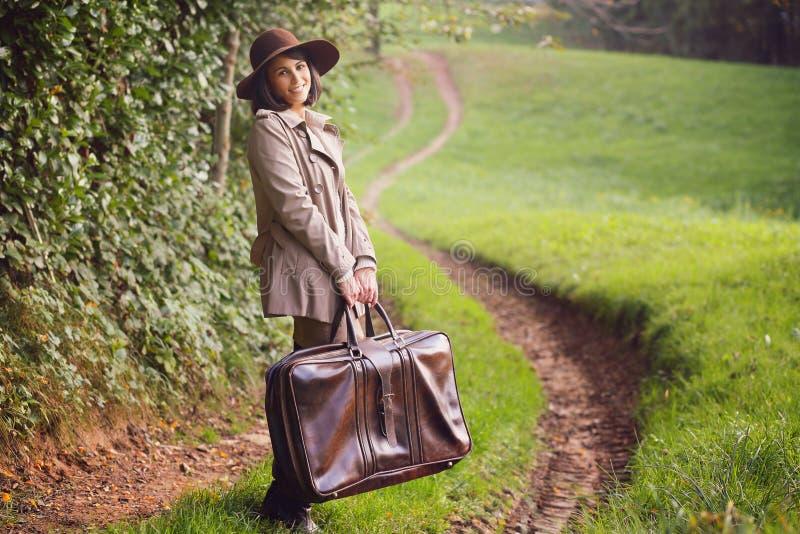 Uśmiechnięta kobieta z rocznik walizką obrazy royalty free