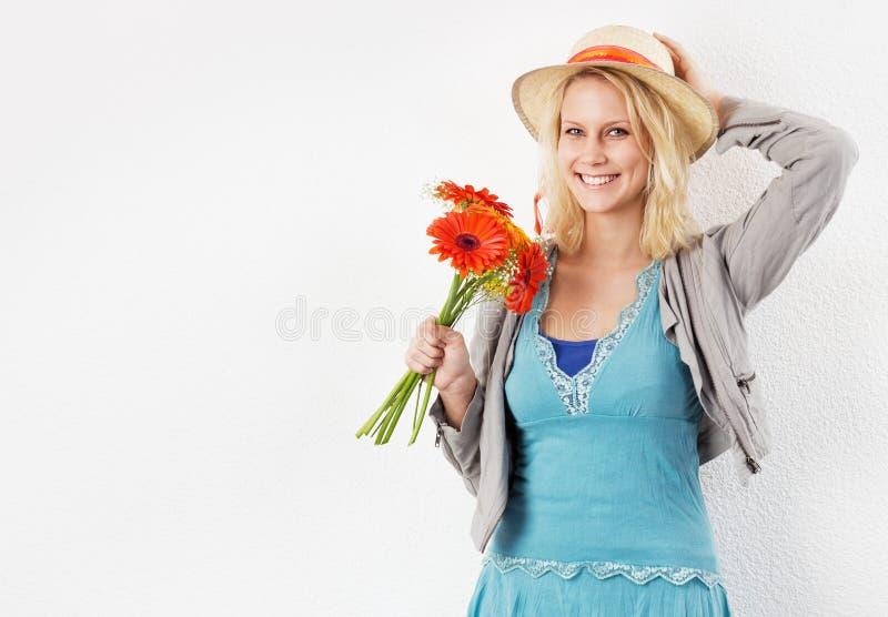 Uśmiechnięta kobieta z słońca kapeluszem i bukietem kwiaty fotografia stock