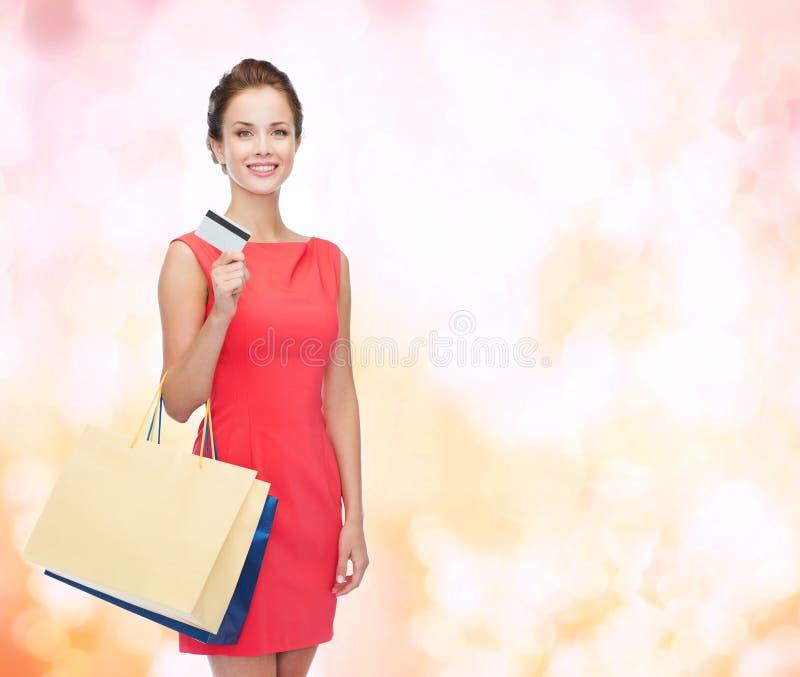 Uśmiechnięta kobieta z torba na zakupy i klingeryt kartą zdjęcie royalty free