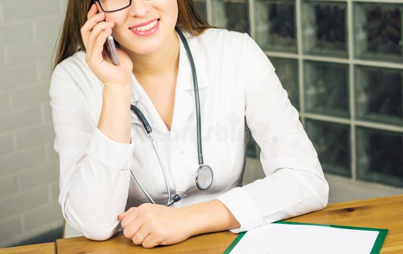 Uśmiechnięta kobiety lekarka Relaksuje przy jej biurem Podczas gdy Dzwoniący Someone Używa telefonu komórkowego zakończenie obrazy stock