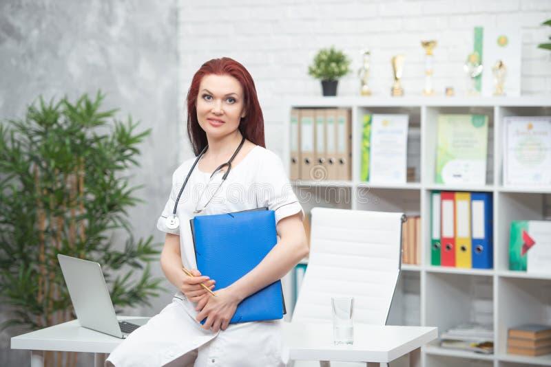 Uśmiechnięta kobiety lekarka w mundurze z stetoskopem i błękitnej falcówce w jej rękach stoi w jego medycznym biurze i spotyka zdjęcie royalty free