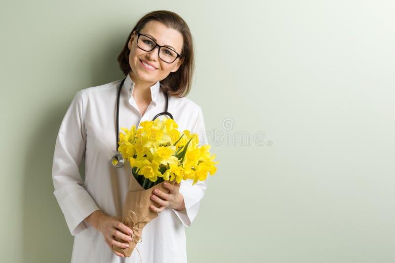 Uśmiechnięta kobiety lekarka z bukietem kwiaty zdjęcie royalty free