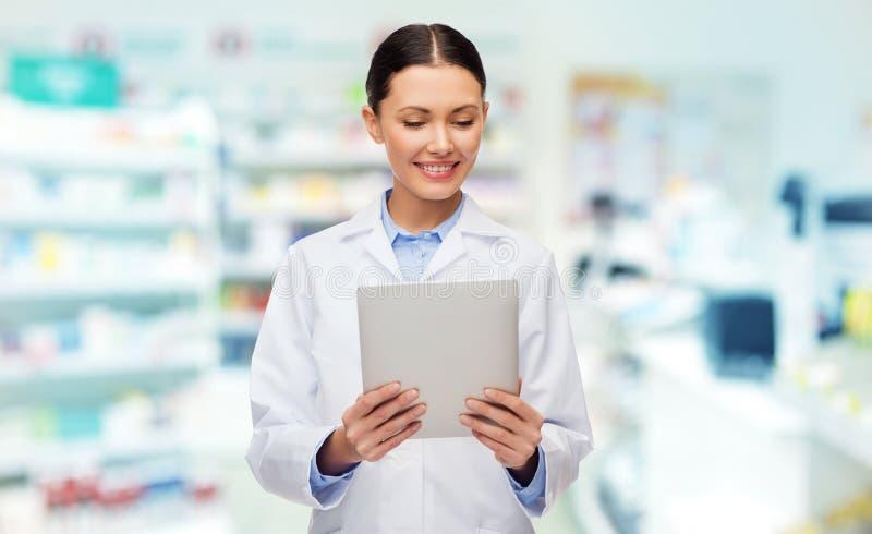 Uśmiechnięta kobiety lekarka z pastylka komputerem osobistym przy apteką fotografia stock