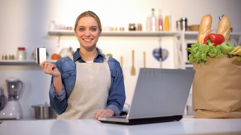 Uśmiechnięta kobiety mienia karta kredytowa w kuchni, karmowym zakupie i dostawie, online obrazy stock
