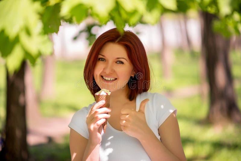 Uśmiechnięta kobiety pozycja pod drzewami w parku lub lesie z dużym seansu kciukiem w górę i lody Cieszyć się momentu i lata czas zdjęcie stock