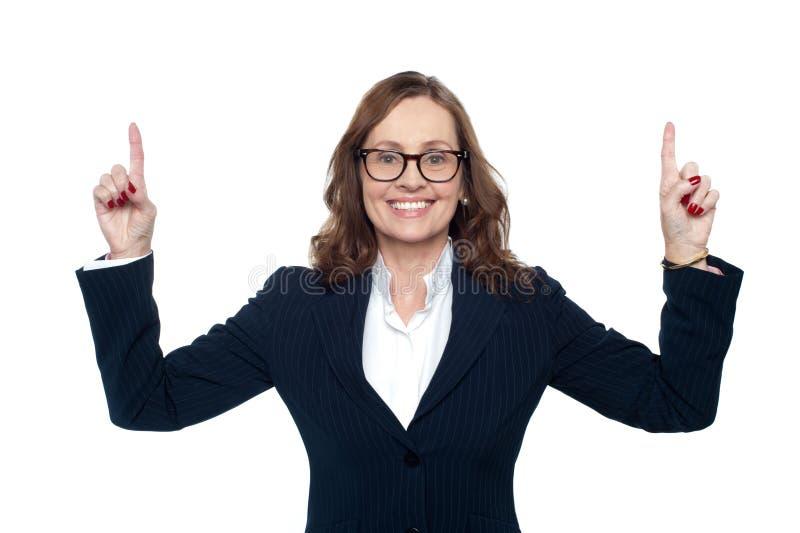 Uśmiechnięta korporacyjna kobieta wskazuje upwards zdjęcia stock
