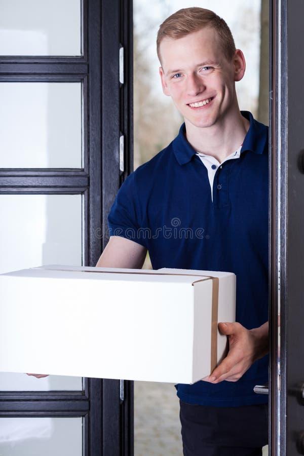Uśmiechnięta kurier pozycja przy drzwi obraz stock