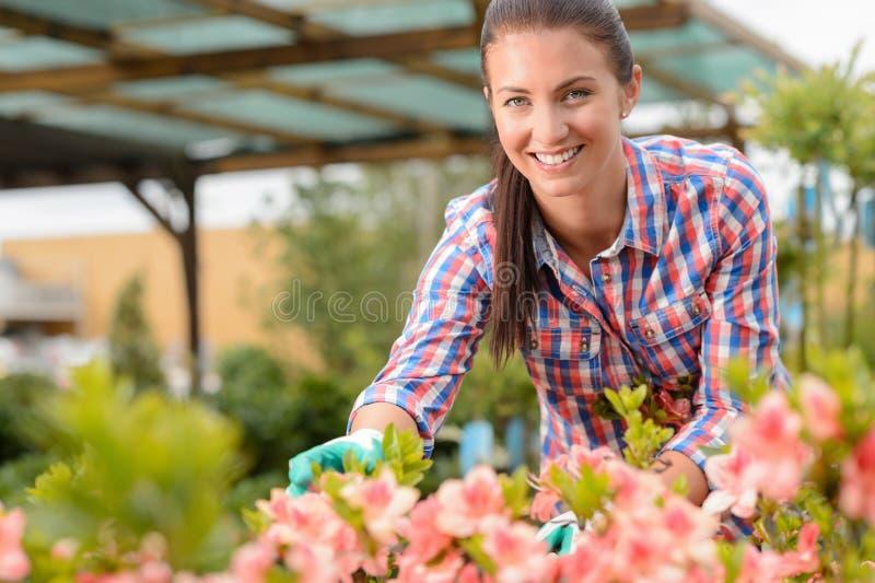 Uśmiechnięta kwiaciarnia pracuje w ogrodowym centrum obraz royalty free