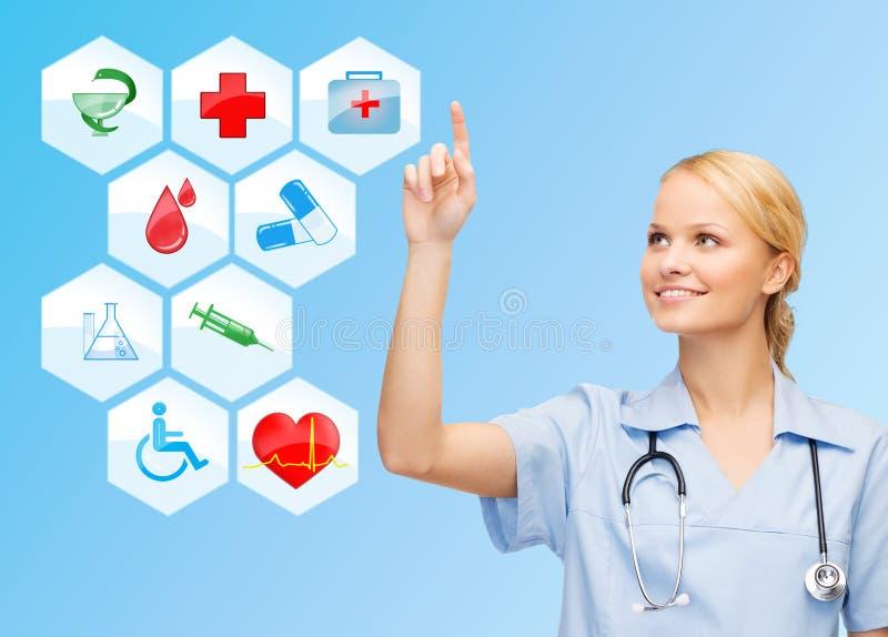 Uśmiechnięta lekarka nad medycznym ikony błękita tłem obrazy stock