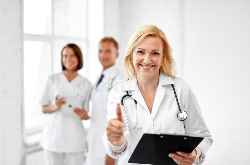 Uśmiechnięta lekarka pokazuje aprobaty przy szpitalem zdjęcia royalty free
