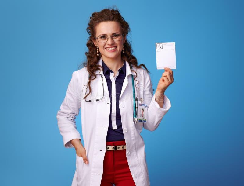 Uśmiechnięta lekarz medycyny kobieta pokazuje receptę na błękicie fotografia stock