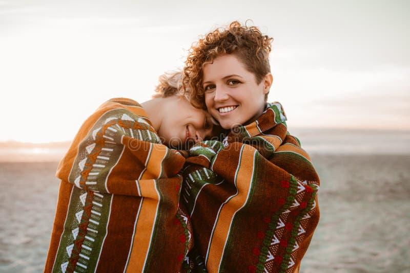 Uśmiechnięta lesbian para zawijająca w plażowej koc przy zmierzchem obrazy royalty free