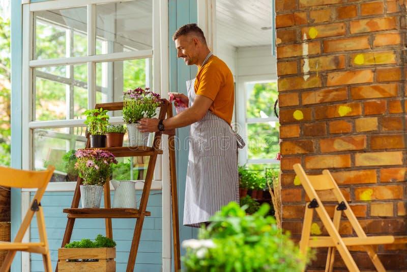 Uśmiechnięta mężczyzna pozycja blisko kwiatu i opryskiwanie rośliien odkłada fotografia royalty free