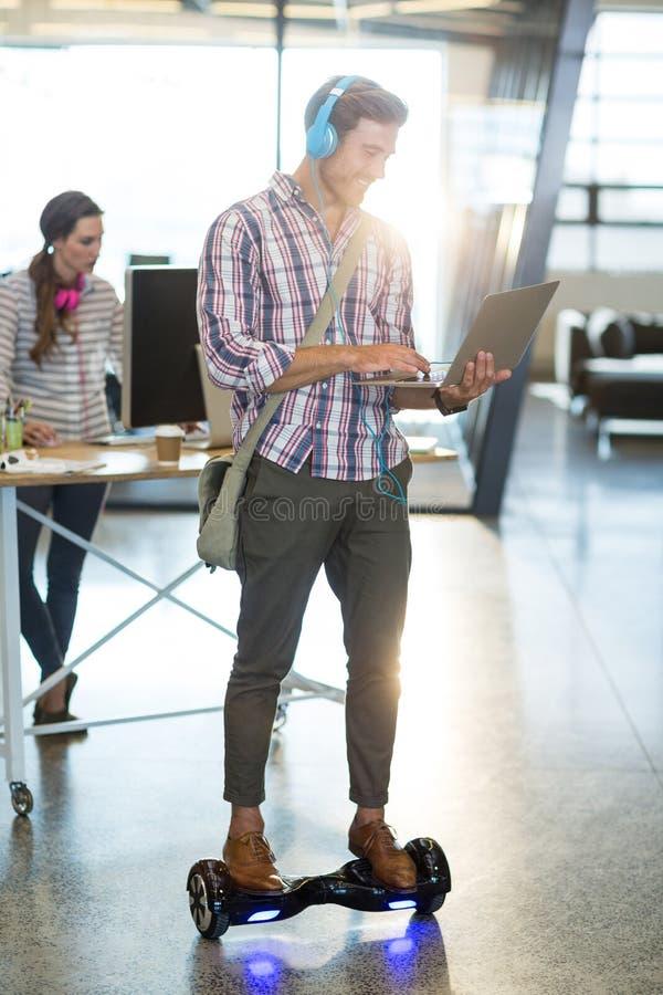 Uśmiechnięta mężczyzna pozycja na hoverboard i używać laptopie obraz stock