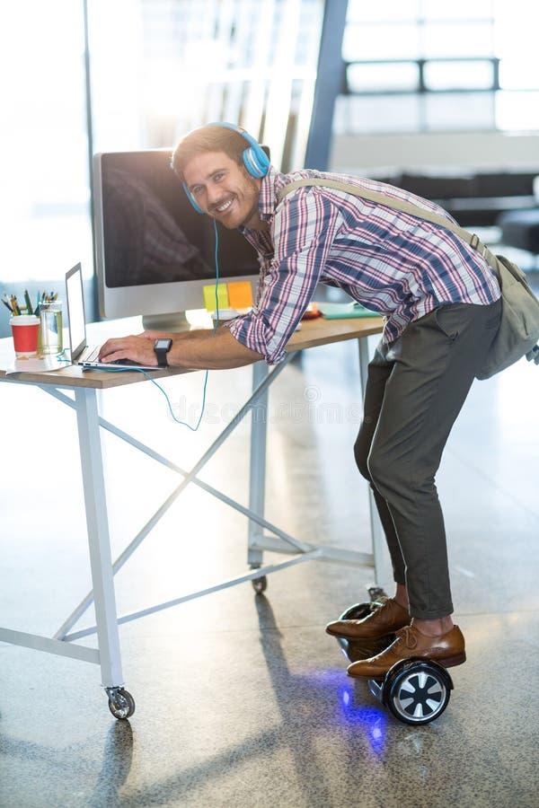 Uśmiechnięta mężczyzna pozycja na hoverboard i używać laptopie w biurze zdjęcie stock