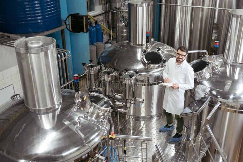 Uśmiechnięta mężczyzna pozycja w maszynerii przy piwną fabryką obrazy royalty free