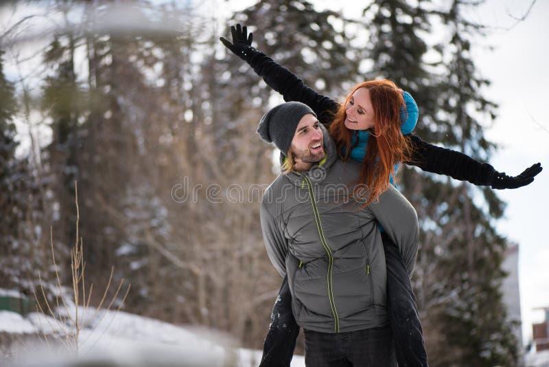 Uśmiechnięta mężczyzna przewożenia dziewczyna na jego z powrotem zdjęcie royalty free