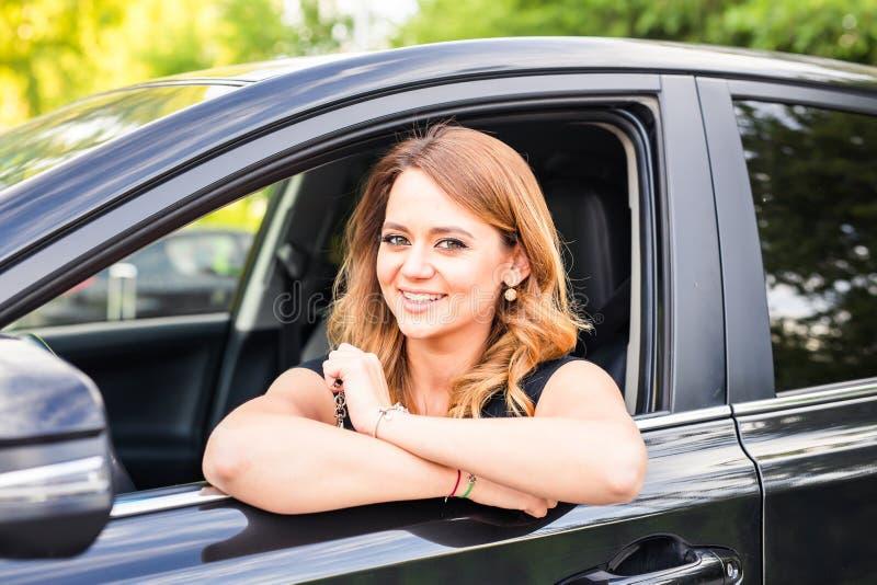 Uśmiechnięta młoda ładna kobieta w czarnym samochodzie Pojęcie podróż, czynszowy samochód lub kupienie samochód, fotografia royalty free