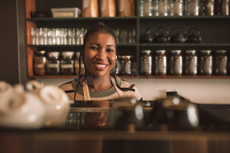 Uśmiechnięta młoda Afrykańska barista pozycja za cukiernianym kontuarem obrazy royalty free