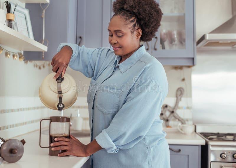 Uśmiechnięta młoda Afrykańska kobieta przygotowywa świeżą kawę w jej kuchni obraz royalty free