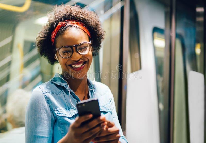 Uśmiechnięta młoda Afrykańska kobieta słucha muzyka na ona dojeżdżać do pracy obrazy royalty free