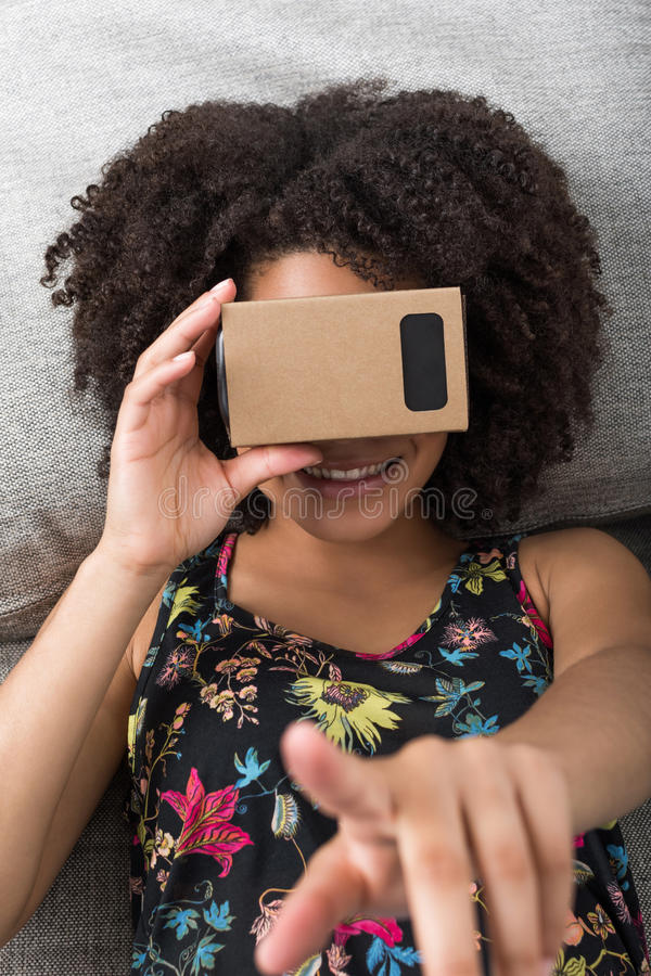Uśmiechnięta młoda Afrykańska kobieta używa rzeczywistość wirtualna przyrząd obrazy royalty free