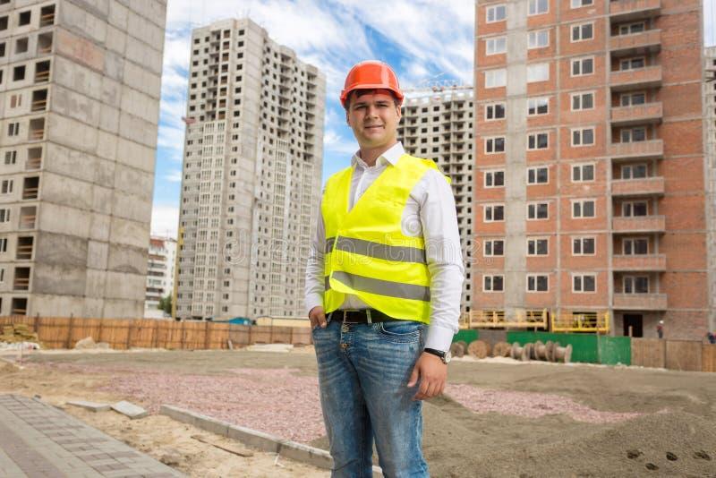 Uśmiechnięta młoda architekt pozycja przy budynkami w budowie zdjęcia royalty free