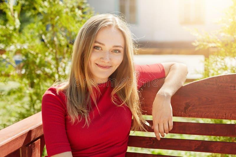 Uśmiechnięta młoda atrakcyjna kobieta jest ubranym elegancką czerwień z długiego prostego lekkiego włosy ciepłymi oczami i dimple obraz royalty free