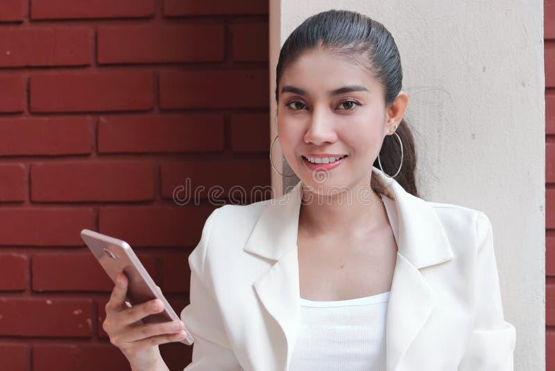 Uśmiechnięta młoda Azjatycka kobieta z mobilnym mądrze telefonem w ona ręki Internet rzeczy pojęcie obrazy royalty free