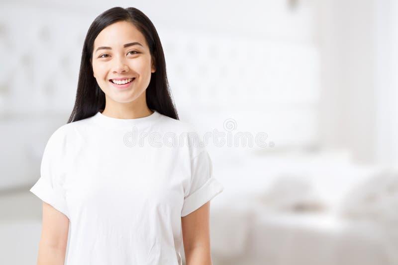 Uśmiechnięta młoda azjatykcia kobieta z doskonalić skóry opieką szablonu t koszula tłem i w domu Pusta t koszula i lata pojęcie k obrazy royalty free