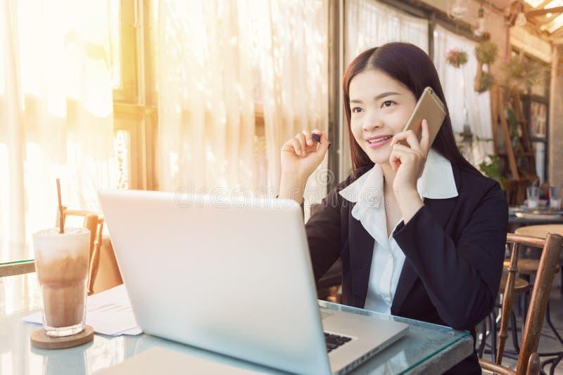Uśmiechnięta młoda azjatykcia wykonawcza biznesowa kobieta pracuje w kawie fotografia stock