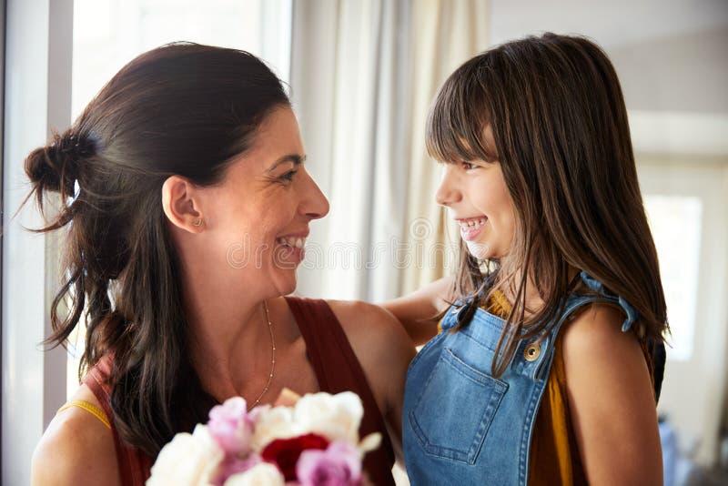 Uśmiechnięta młoda biała dziewczyna daje jej matce wiązce kwiaty na Mother�s dniu, zakończenie w górę obraz royalty free