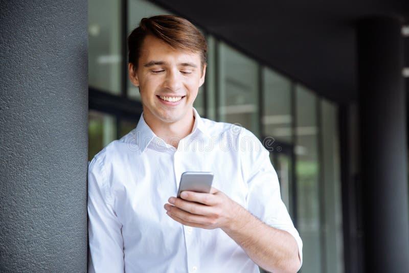 Uśmiechnięta młoda biznesmen pozycja i używać telefon komórkowy fotografia stock