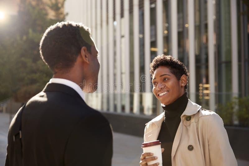 Uśmiechnięta młoda czarna bizneswoman pozycja na ulicie z takeaway kawą, opowiada jej męski kolega, selekcyjna ostrość obraz stock