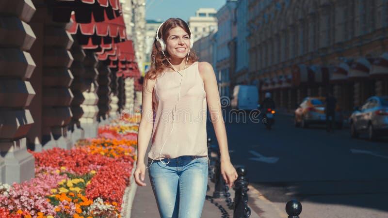 Uśmiechnięta młoda dziewczyna słucha muzyka na ulicie zdjęcie royalty free