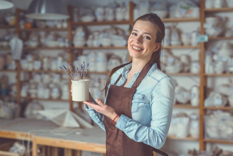 Uśmiechnięta młoda dziewczyna z ceramiczną wazą obrazy stock