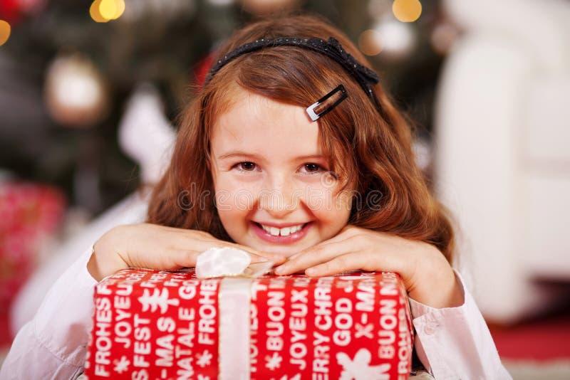 Uśmiechnięta młoda dziewczyna z czerwoną Bożenarodzeniową teraźniejszością zdjęcie royalty free