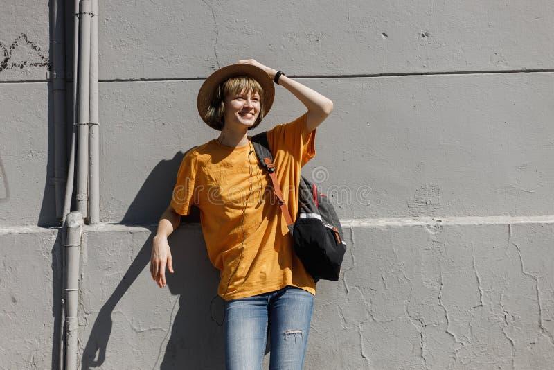 Uśmiechnięta młoda dziewczyna z plecakiem ubierał w żółtej koszulce i słomiany kapelusz stoi opierać na szarym budynku w mieście obrazy royalty free